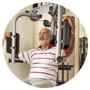 Senior using hydro pneumatic gym equipment at Primus Eden
